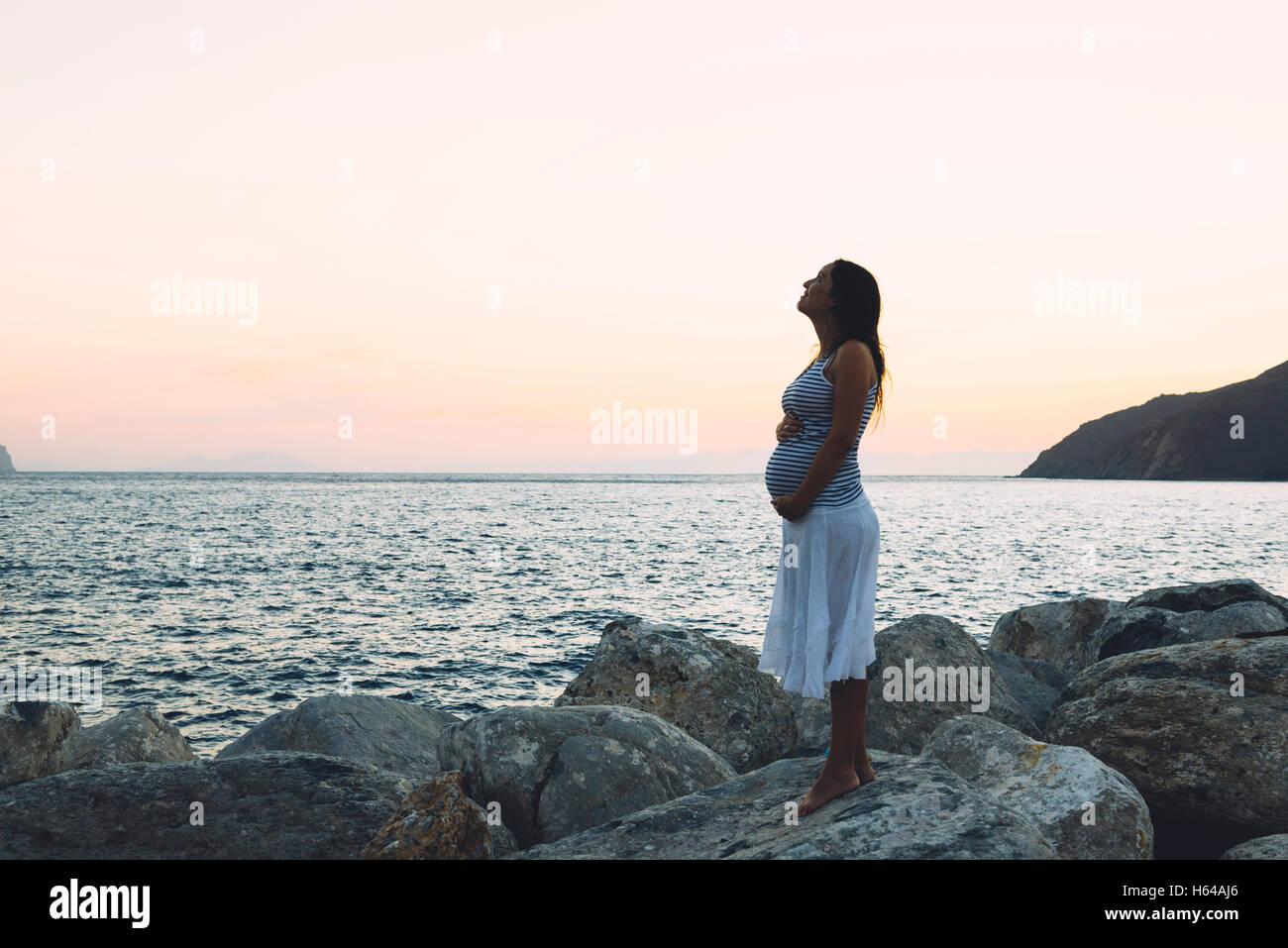 22b23bba5 Mujer embarazada de pie sobre una roca frente al mar al atardecer Imagen De  Stock