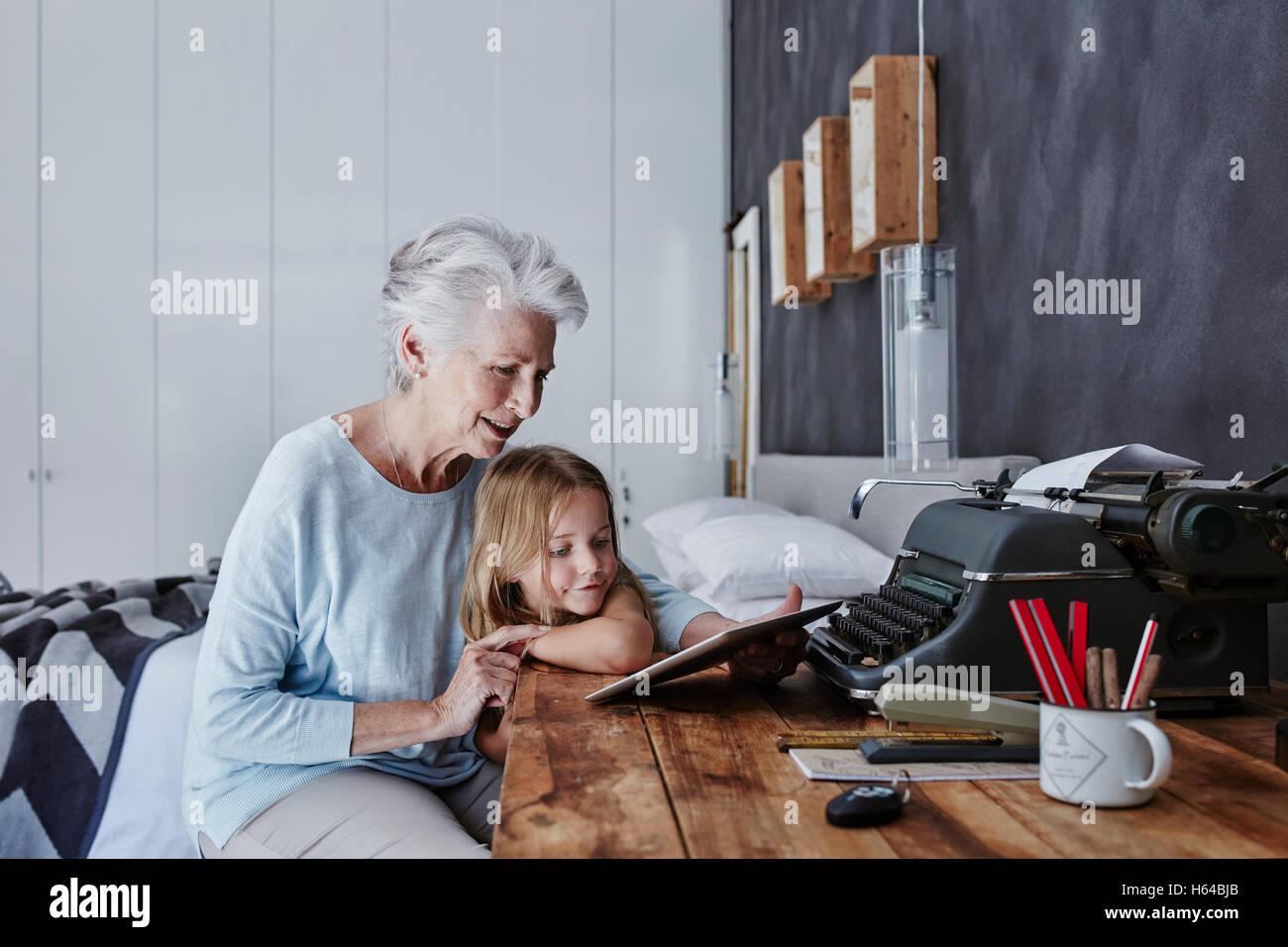 Abuela y nieta mirando tablet en casa Foto de stock