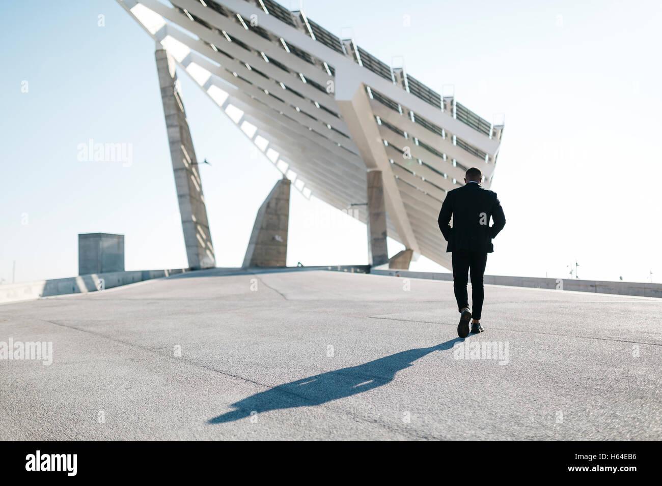 Empresario caminando en paneles solares Imagen De Stock
