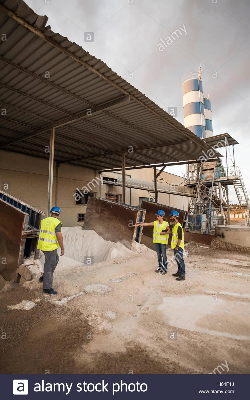 Tres personas en chalecos de seguridad en instalaciones industriales mirando mirando depósitos de arena Imagen De Stock