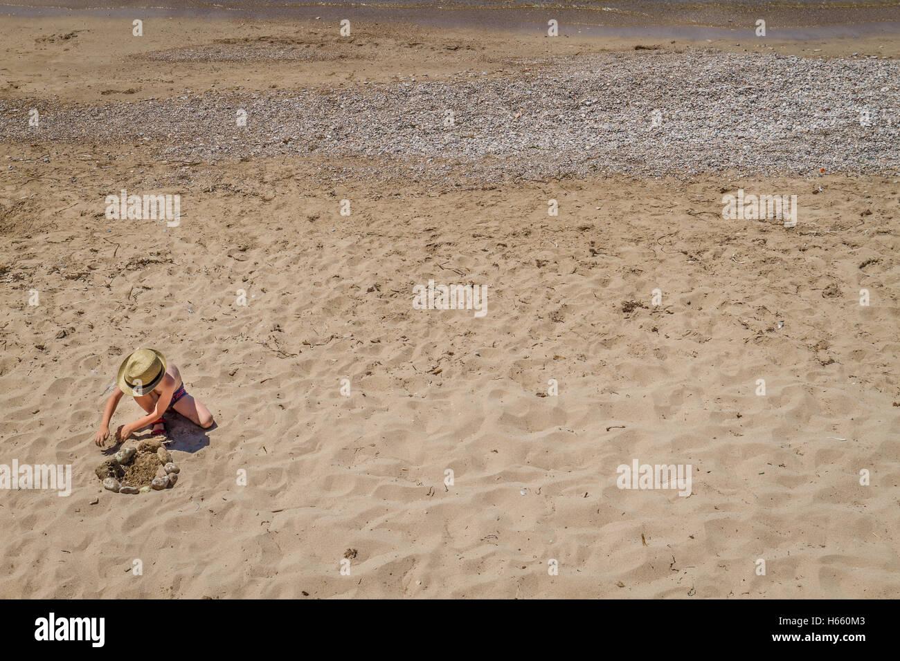 Muchacho jugando con piedras y arena de playa en día soleado Imagen De Stock