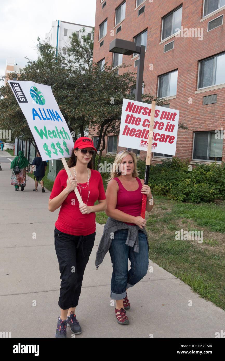Las enfermeras en la línea de piquete que llevaban pancartas protestando por su nuevo paquete de beneficios Imagen De Stock