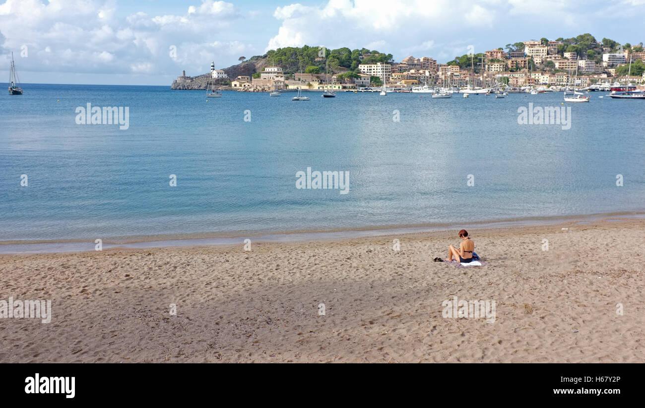 Una mujer sunbathes en una playa desierta, en Sóller, Mallorca Imagen De Stock