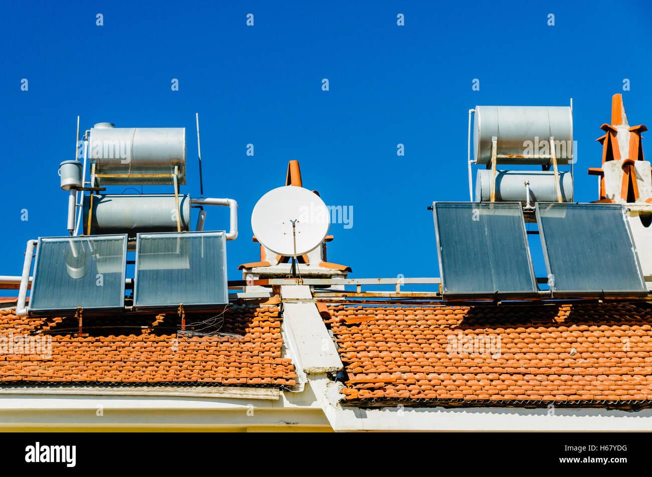 Los calentadores de agua solares y antenas parabólicas en el tejado de un edificio.En un clima caliente Imagen De Stock