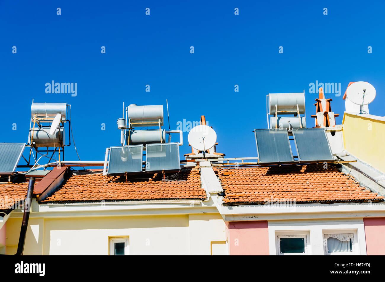 Los calentadores de agua solares y antenas parabólicas en el tejado de un edificio en un clima caliente. Imagen De Stock