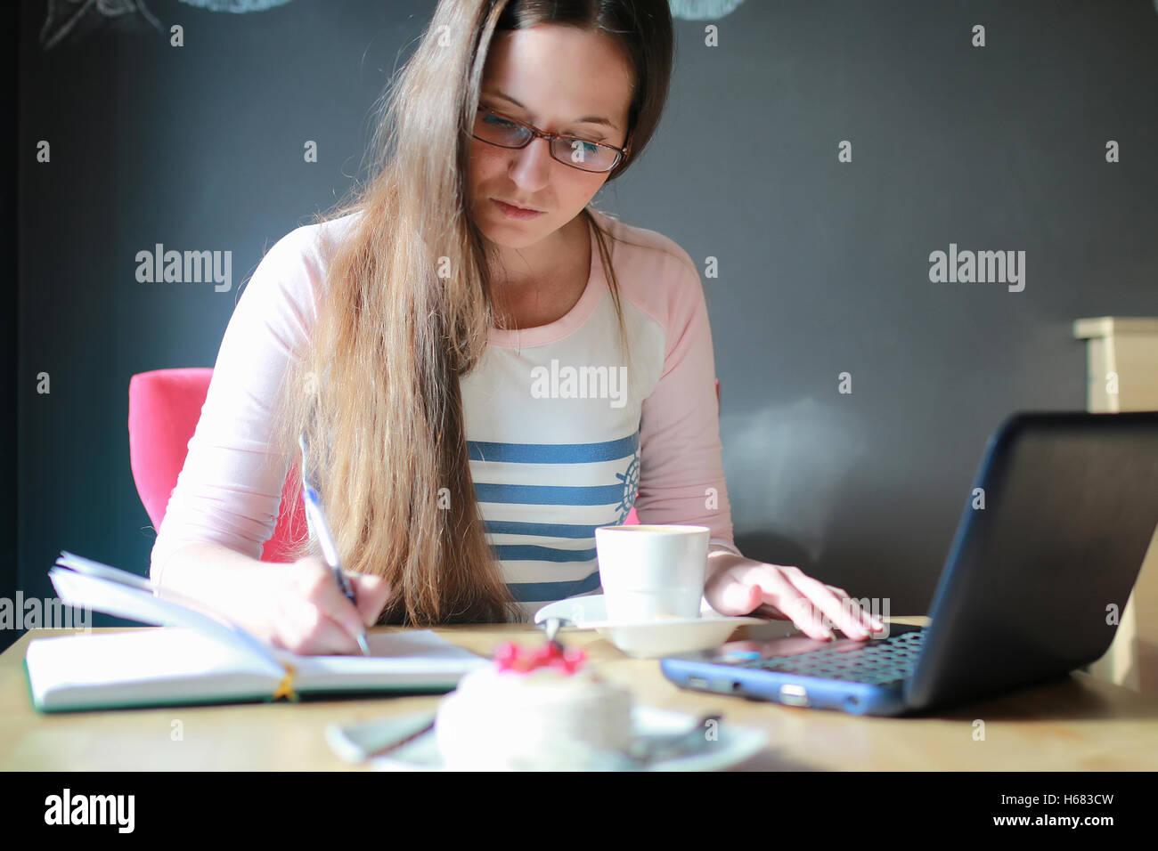 Chica en una cafetería para tomar una taza de café con el portátil Imagen De Stock