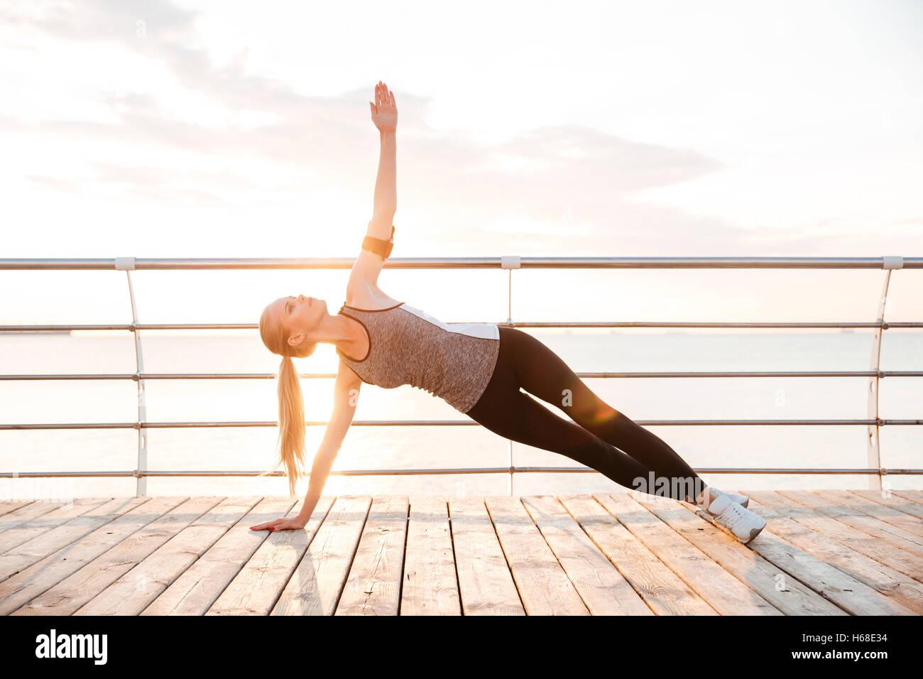 Gimnasio deportivo entarimado mujer realizando ejercicios de yoga al aire libre en el muelle de playa Imagen De Stock