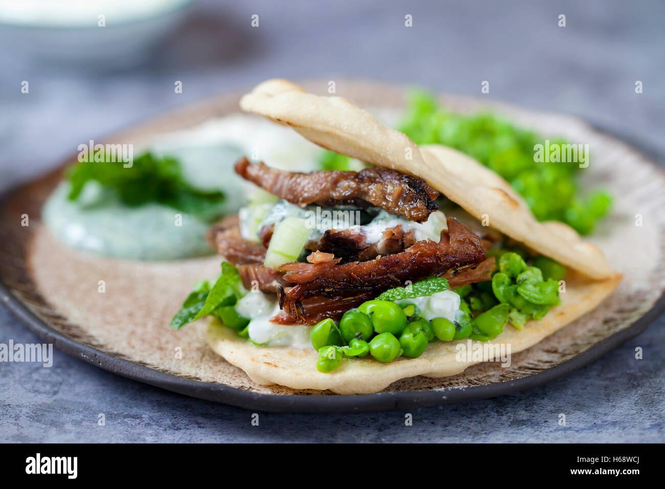 Mini panes planos con crujiente de cordero, puré de guisantes, pepino, menta y salsa de yogur Imagen De Stock