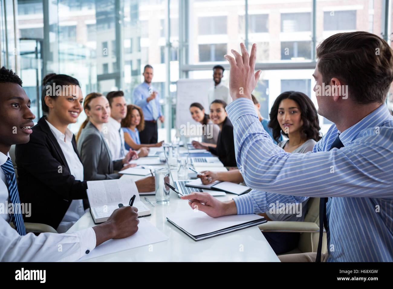 Colega levantando su mano durante la reunión Imagen De Stock