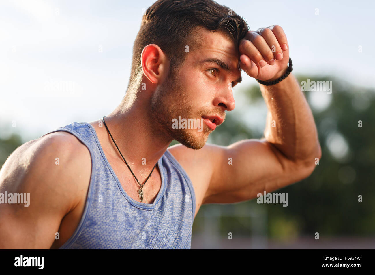 Joven hombre sudoroso muscular después de entrenar fuera de día soleado Imagen De Stock