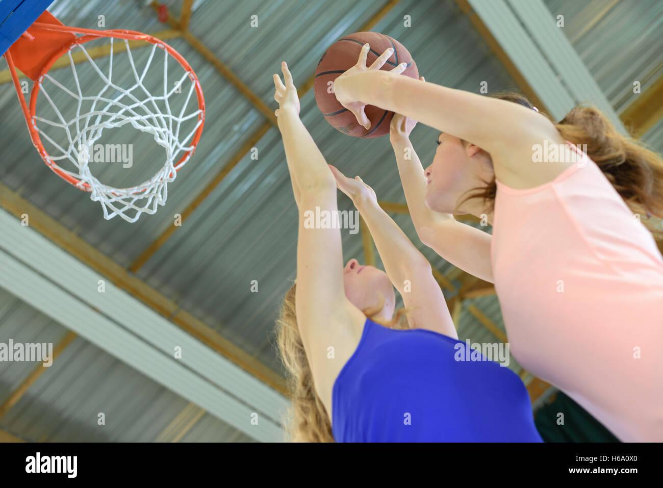 Mujer apuntando hacia el baloncesto net Imagen De Stock