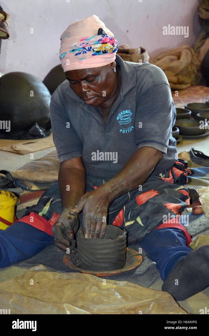 Una mujer demuestra cómo ella crea las ollas de arcilla para venta en la Mukondeni cerámica, en la región de Limpopo Foto de stock