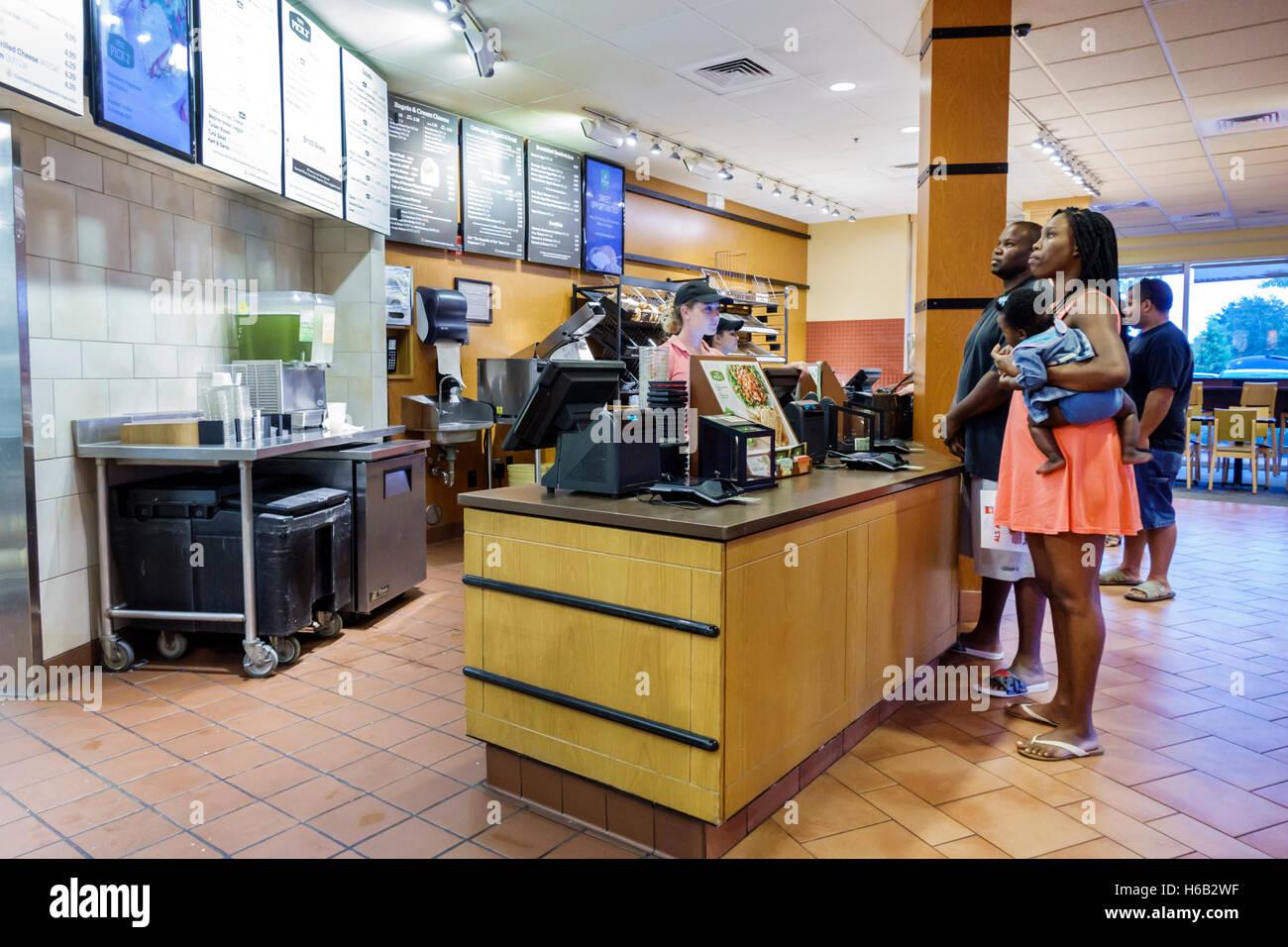 Port St. Lucie Florida Saint Panera Bread interior restaurante contador negro mujer hombre bebé pedido familiar Imagen De Stock