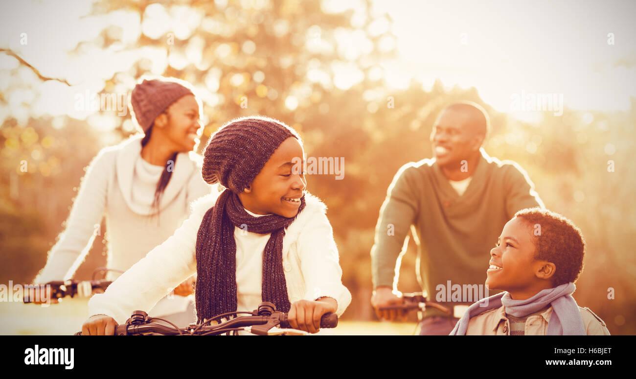 Sonriente joven familia haciendo un paseo en bicicleta Imagen De Stock
