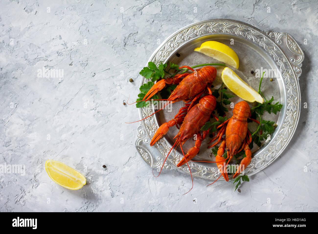 Las langostas cocidas, limón y perejil sobre un fondo de hormigón. Fondo de alimentos. El concepto de Imagen De Stock