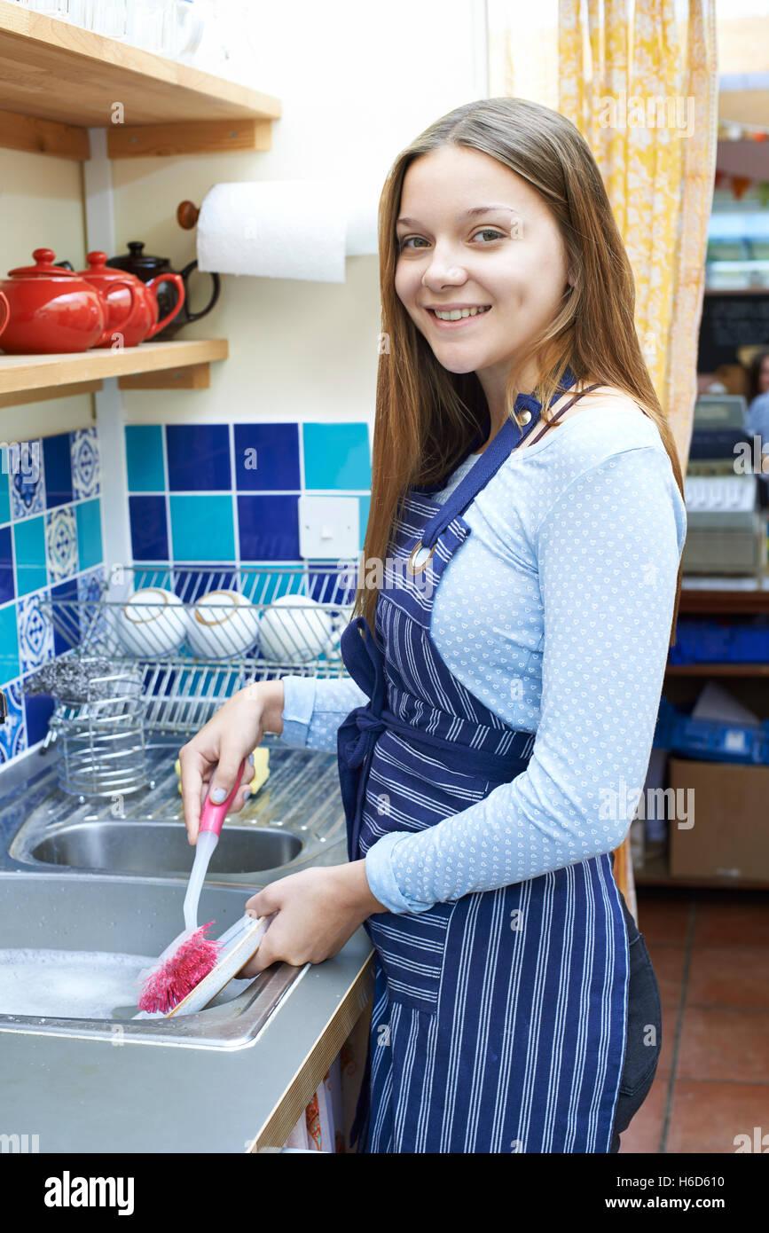 Adolescente con trabajo a tiempo parcial de lavado en la cafetería. Imagen De Stock