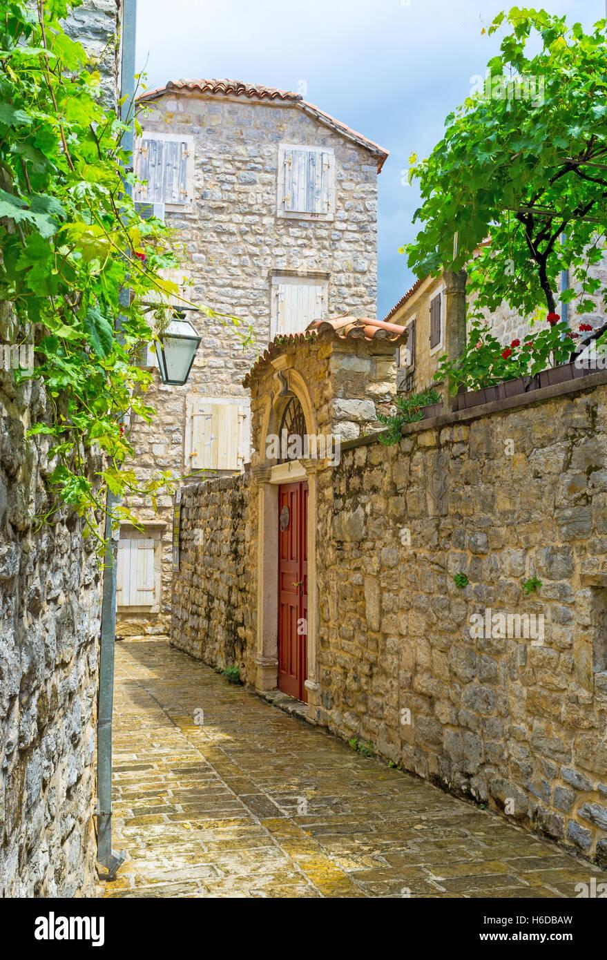 La pintoresca calle medieval con la valla de piedra antigua y la puerta de madera que separa el - Vallas de piedra ...