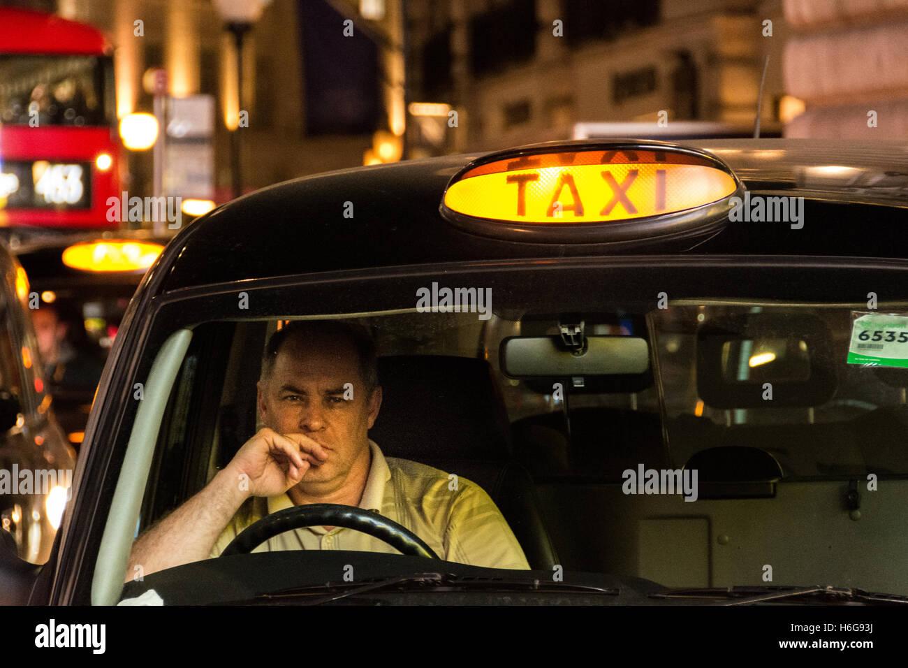 Un conductor de taxi nocturno de aspecto cansado en el West End de Londres Foto de stock
