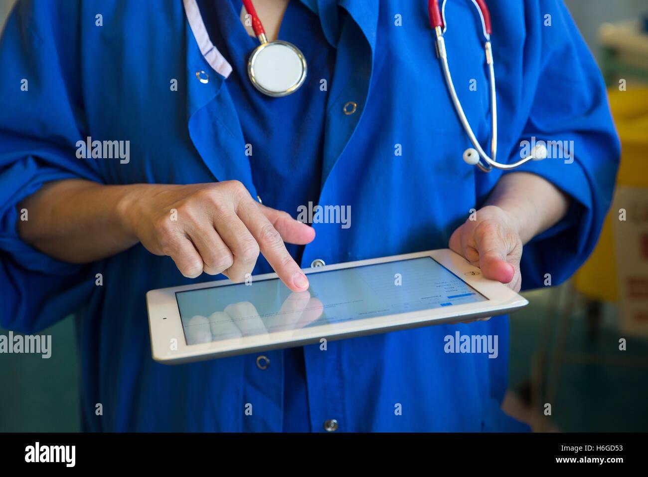 Un médico en una ward comprobaciones a los historiales de los pacientes en un Ipad Imagen De Stock