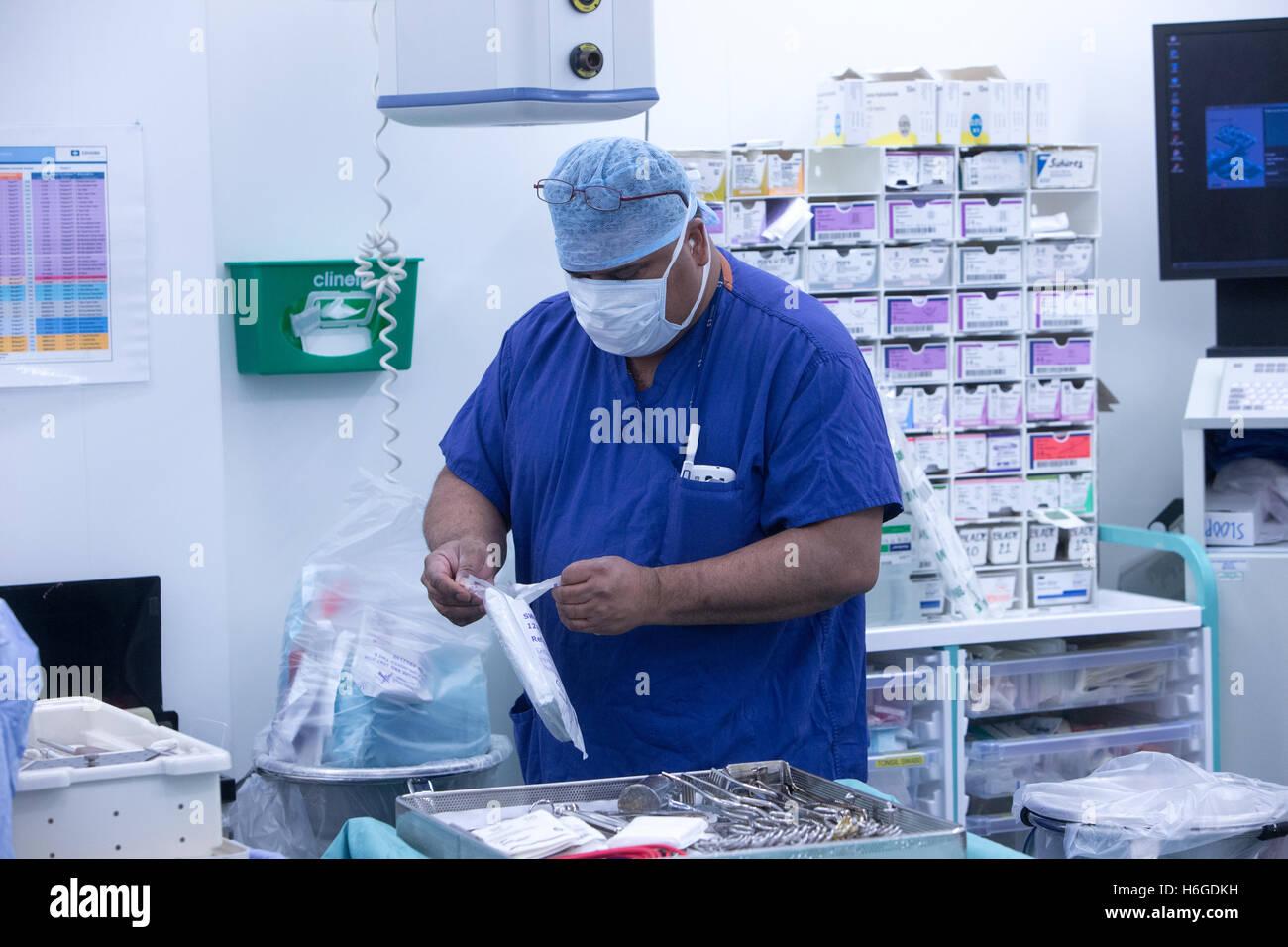 Una enfermera en scrubs abre los paquetes estériles en el quirófano de un hospital durante una operación Foto de stock
