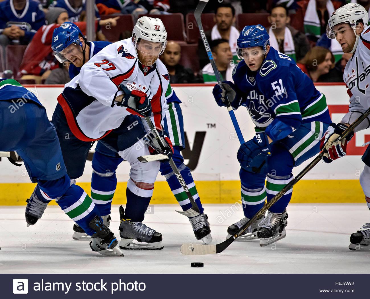 Vancouver. 30 Oct, 2016. Capitales de Washington' Karl Alzner (delantero, L) compite por el puck con Vancouver Imagen De Stock