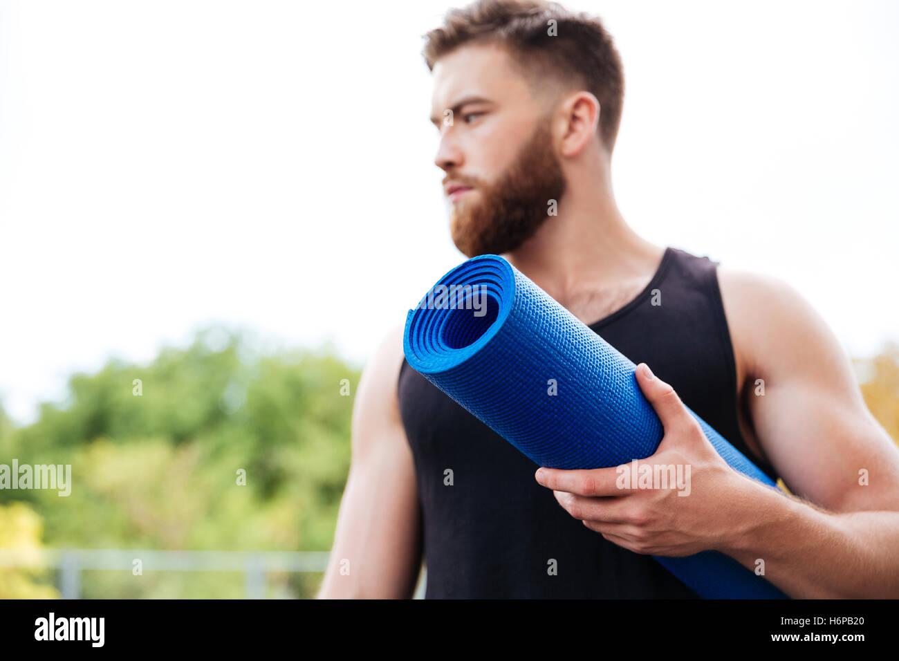 Instructor de yoga masculina grave explotación mat y apartar la mirada de pie afuera Imagen De Stock