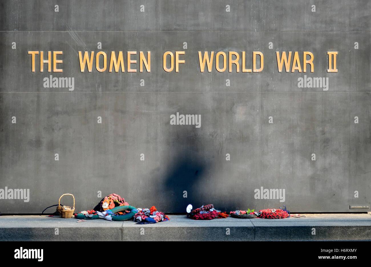Londres, Inglaterra, Reino Unido. Las mujeres de la II Guerra Mundial memorial en Whitehall. Coronas de flores y una cesta de flores izquierda Foto de stock