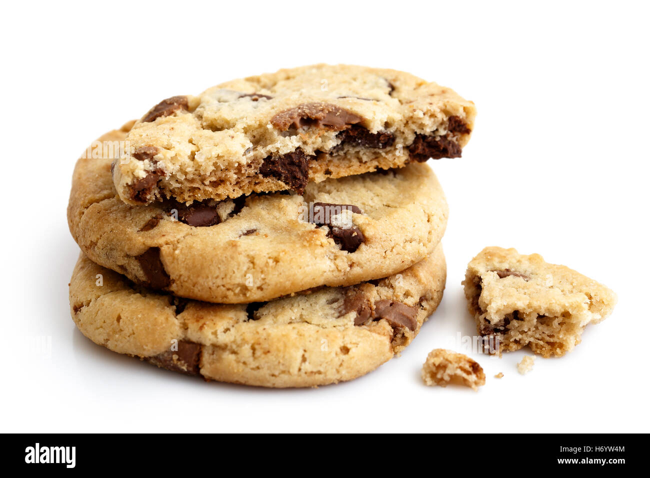 Una pila de tres galletas con trocitos de chocolate de luz aislados. La mitad con migas. Foto de stock