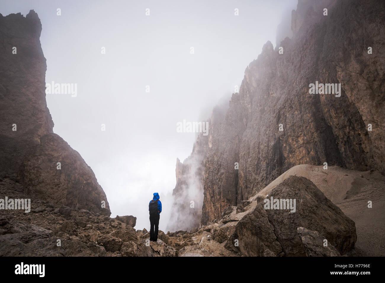 Mujer joven de pie en las montañas Dolomitas, Val Gardena, Tirol del Sur, Italia Foto de stock