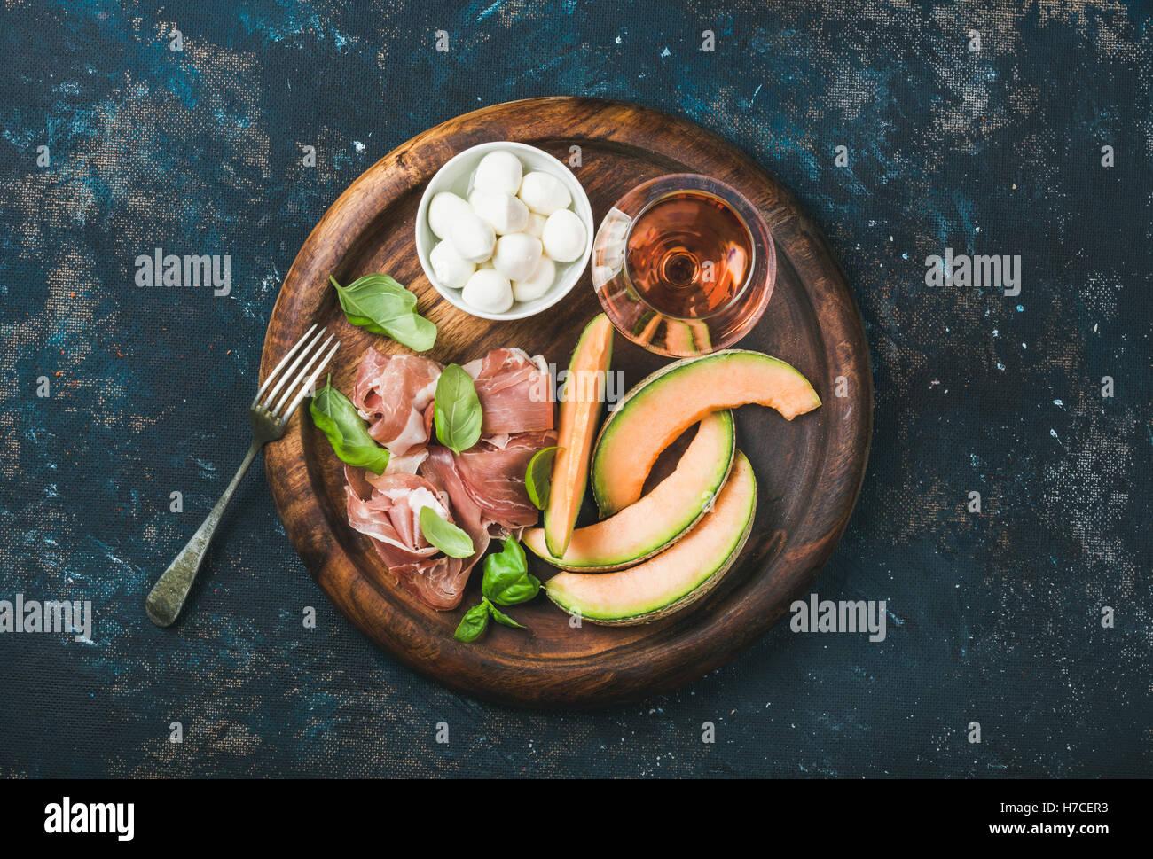 Prosciutto di Parma, melón, queso mozzarella en un recipiente, hojas de albahaca fresca y una copa de vino Imagen De Stock