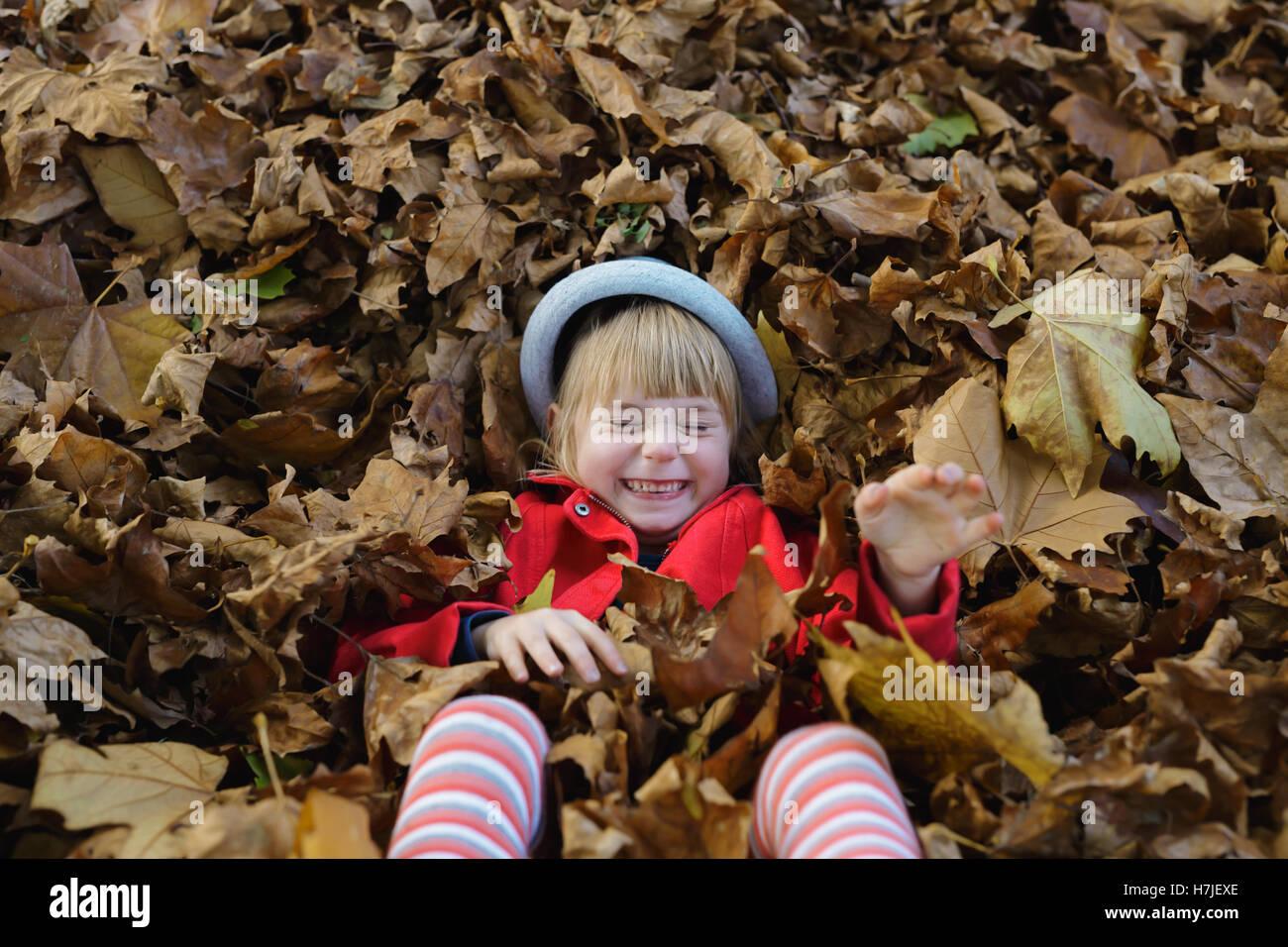 Feliz otoño. Niña chaqueta roja jugando con la pila de hojas secas en otoño del parque. Foto de stock