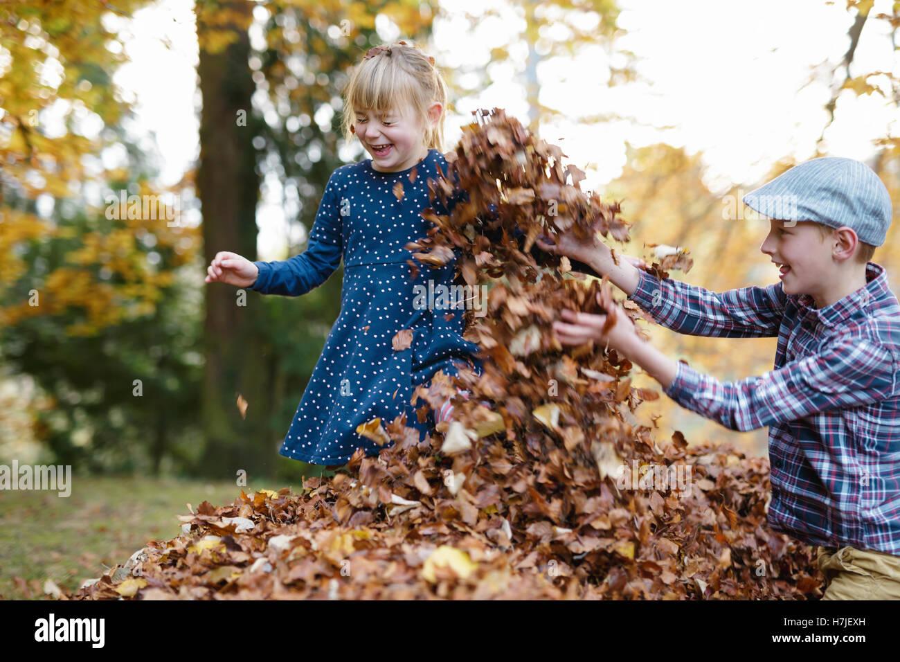 Feliz otoño. Dos niños jugando en el montón de hojas secas en otoño del parque. Foto de stock