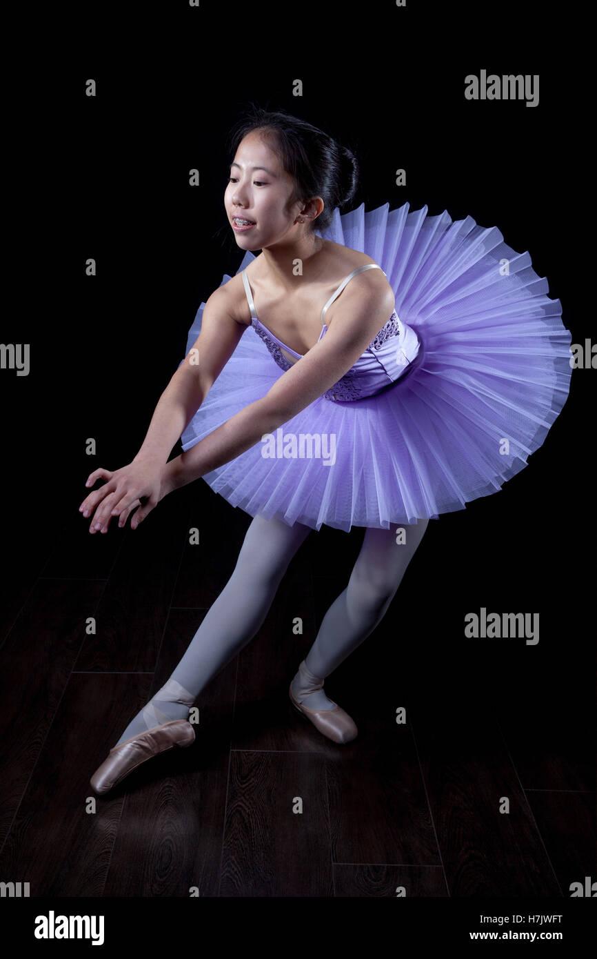 Joven bailarina vistiendo pointe zapatos y tutu en pose de baile. Imagen De Stock