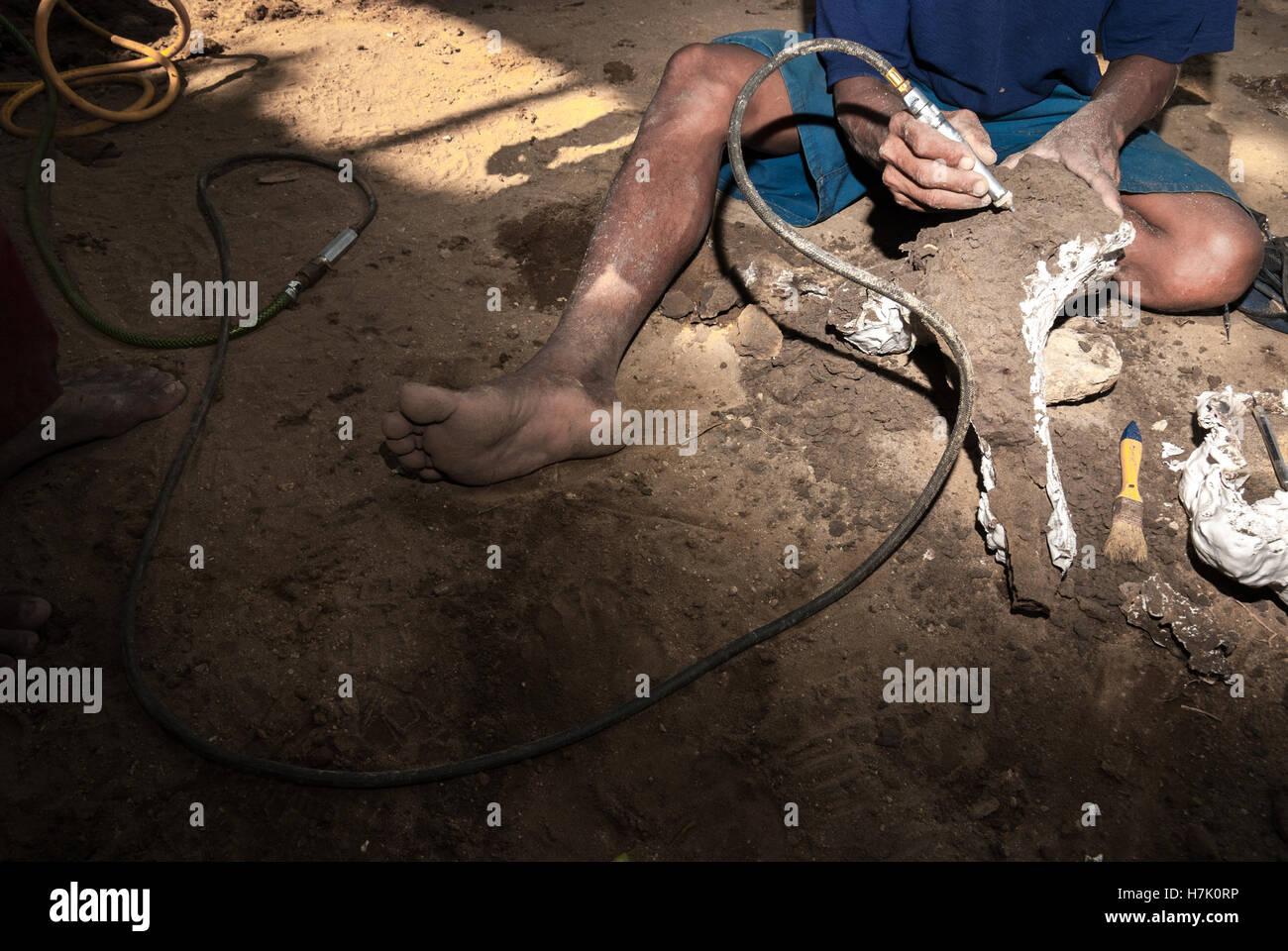 El trabajador es mediante aire abrasivo para limpiar una herramienta envuelto fósil. Imagen De Stock