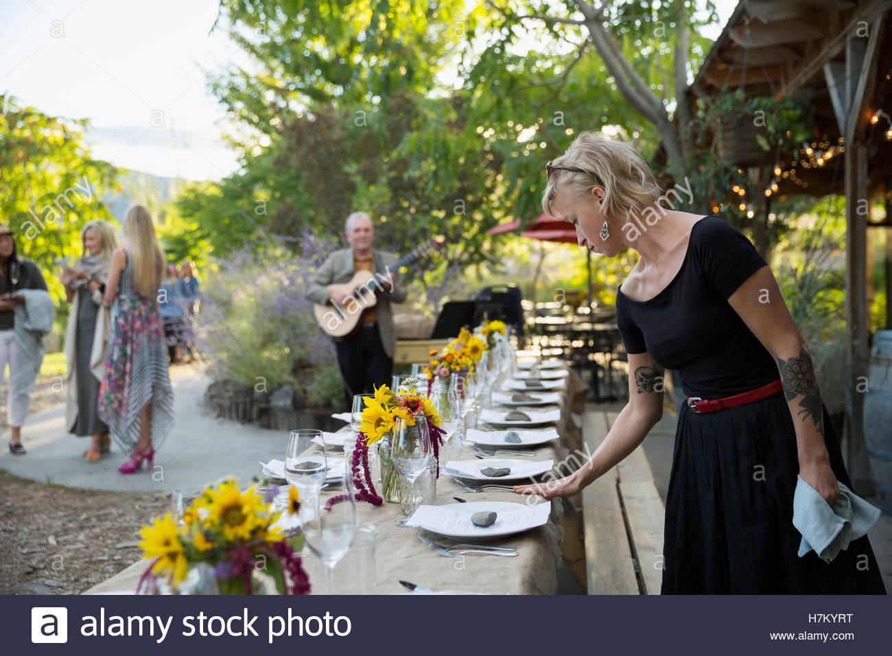Camarera preparando la cena placesettings cosecha en larga mesa de patio Imagen De Stock