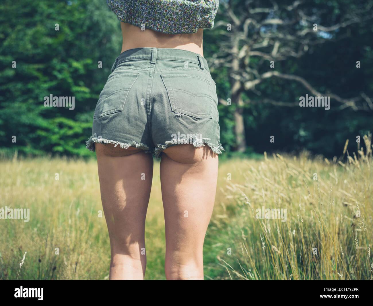 Vista Trasera De Una Joven Mujer Vistiendo Pantalones Muy Cortos Y De Pie En Un Prado En Un Dia De Verano Fotografia De Stock Alamy