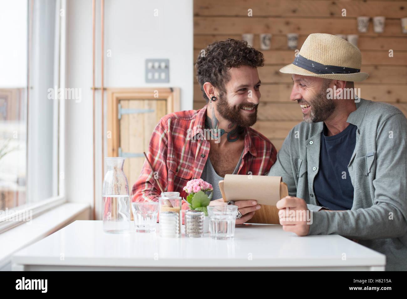 Una pareja gay sat menú de visualización en cafe Imagen De Stock