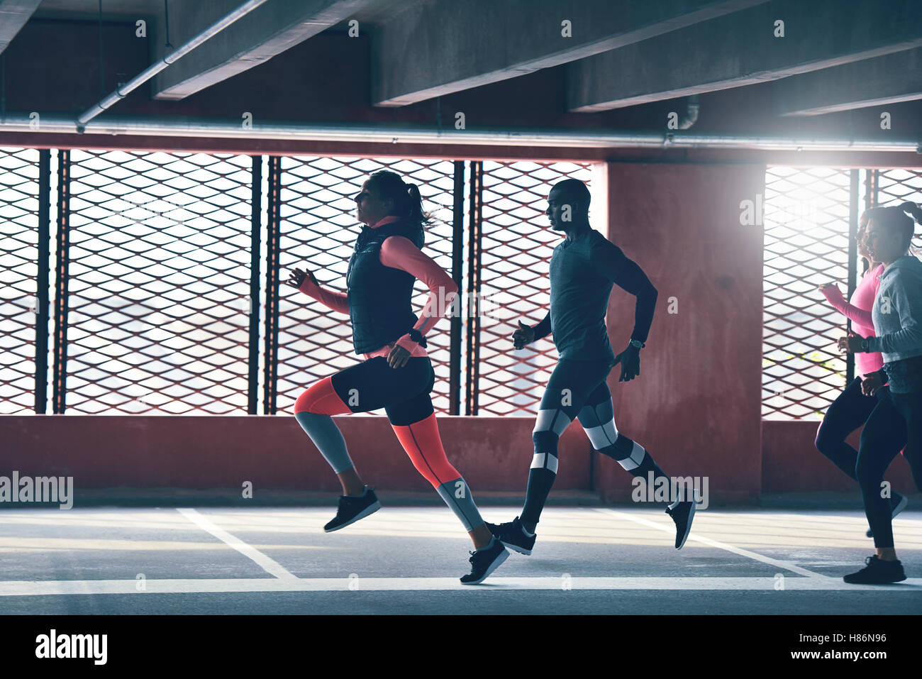 Vista lateral de los jóvenes atletas ejercicio delante de grandes ventanales. Copyspace Imagen De Stock
