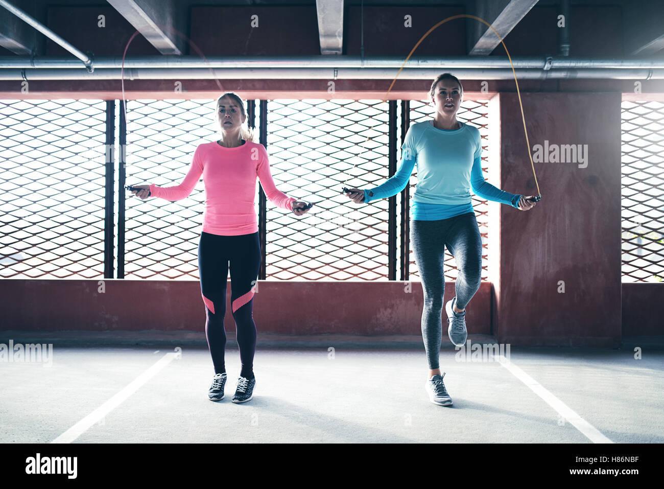 Vista frontal del Athletic dos chicas haciendo ejercicio copyspace saltar la cuerda. Imagen De Stock