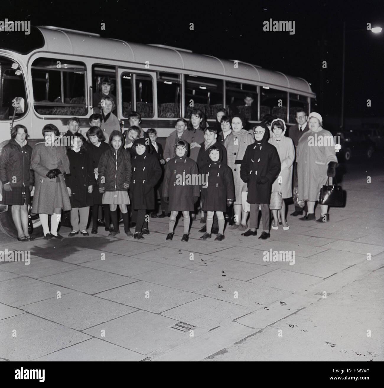1965, histórica, por la tarde y un grupo de niños entusiasmados en abrigos de invierno con adultos acompañantes Imagen De Stock