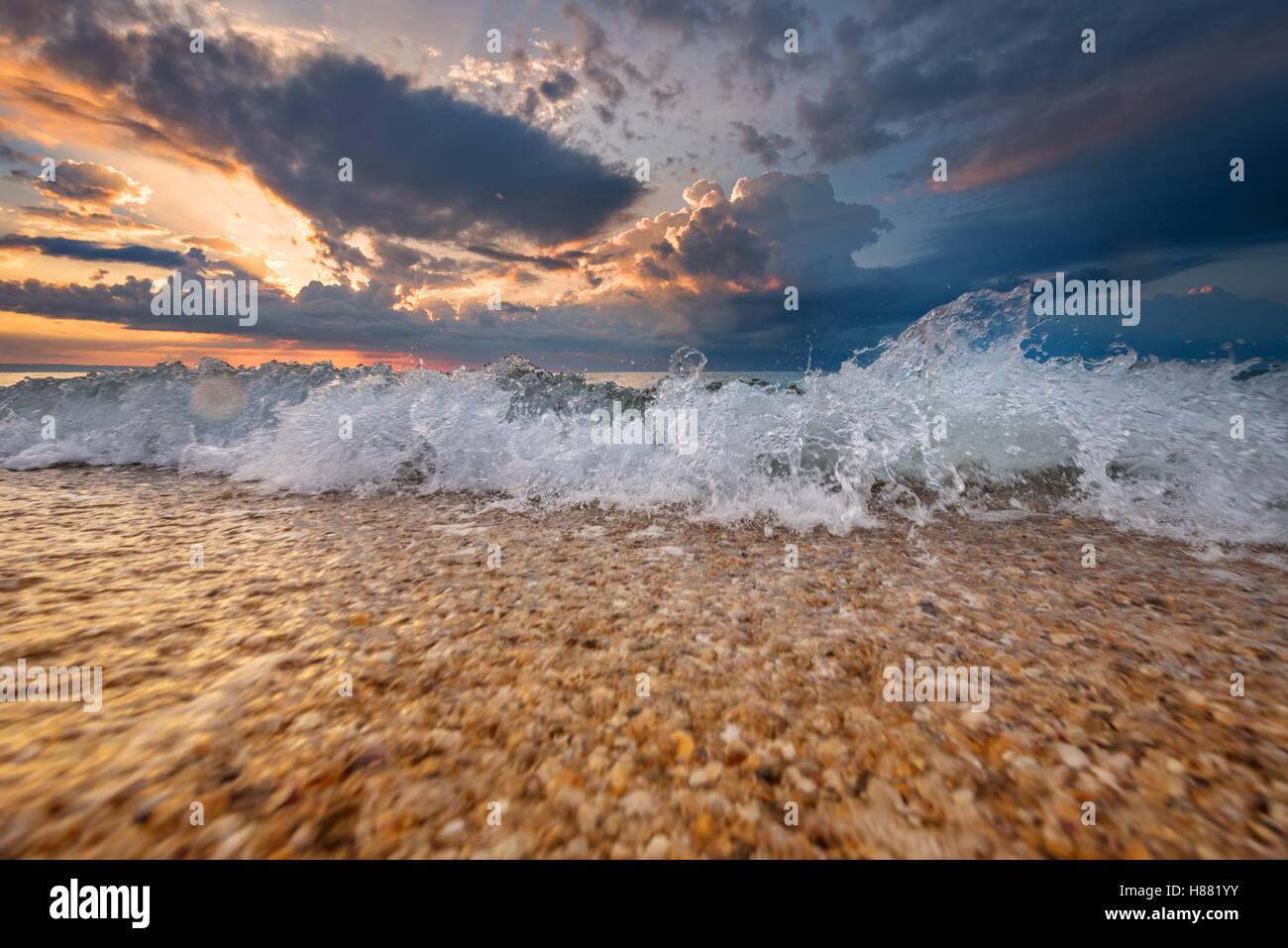 Colorido destino de playa un amanecer o atardecer con hermosas olas Foto de stock