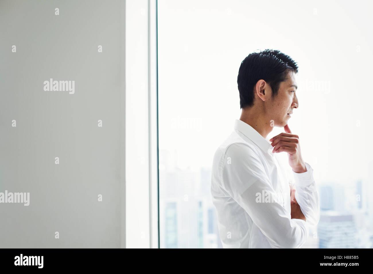 Un empresario en la oficina de pie junto a una ventana grande con brazos cruzados, mirando hacia la ciudad. Foto de stock