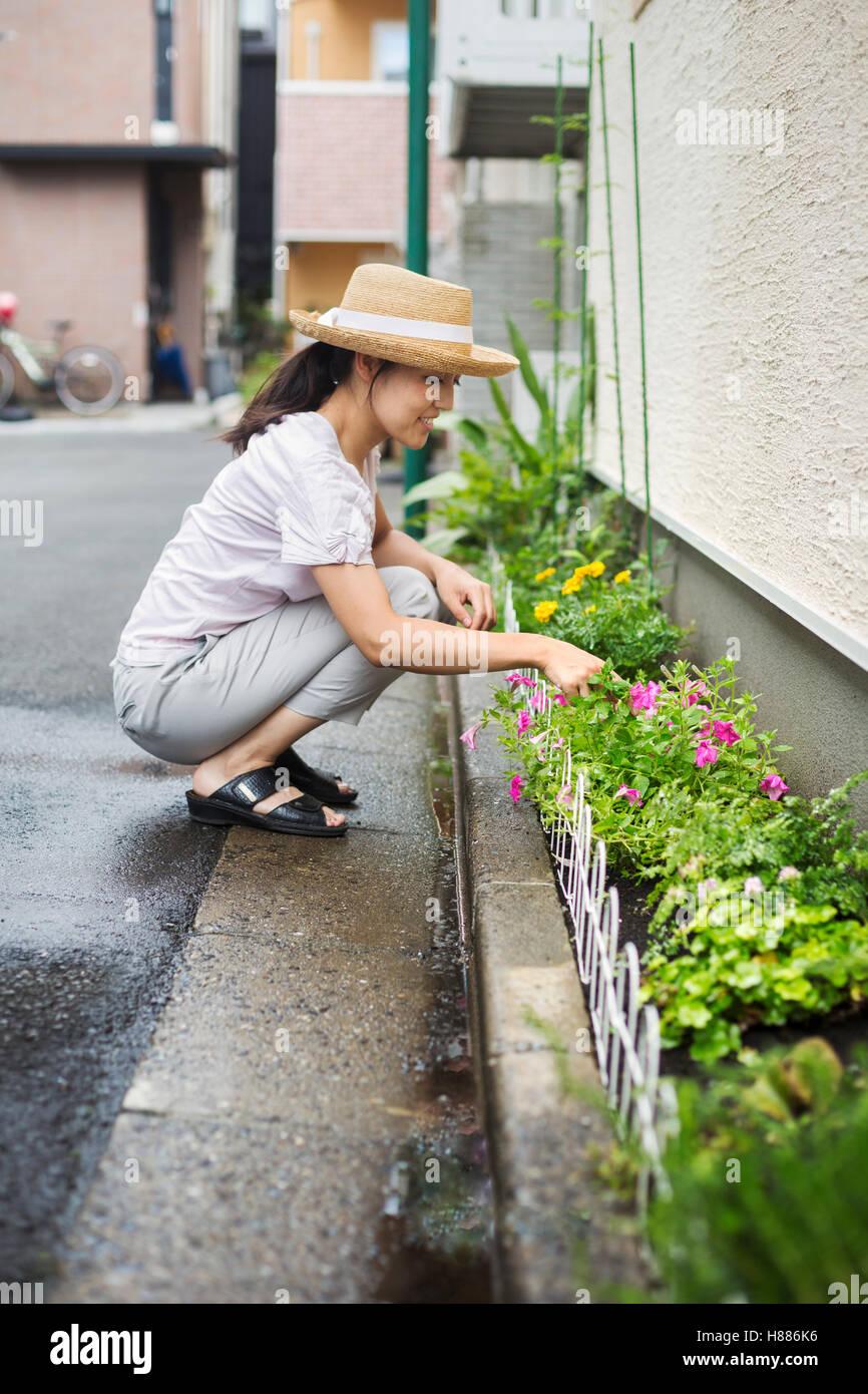 Casa de familia. Una mujer en cuclillas y plantar flores en una pequeña franja de tierra. Imagen De Stock