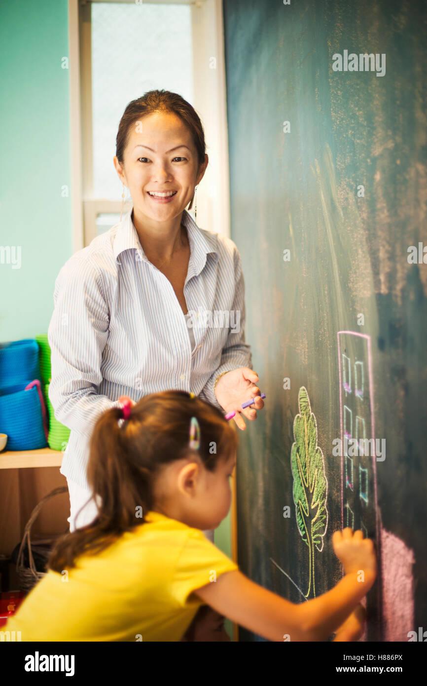 Un niño escribe en la pizarra y un profesor a su lado. Foto de stock