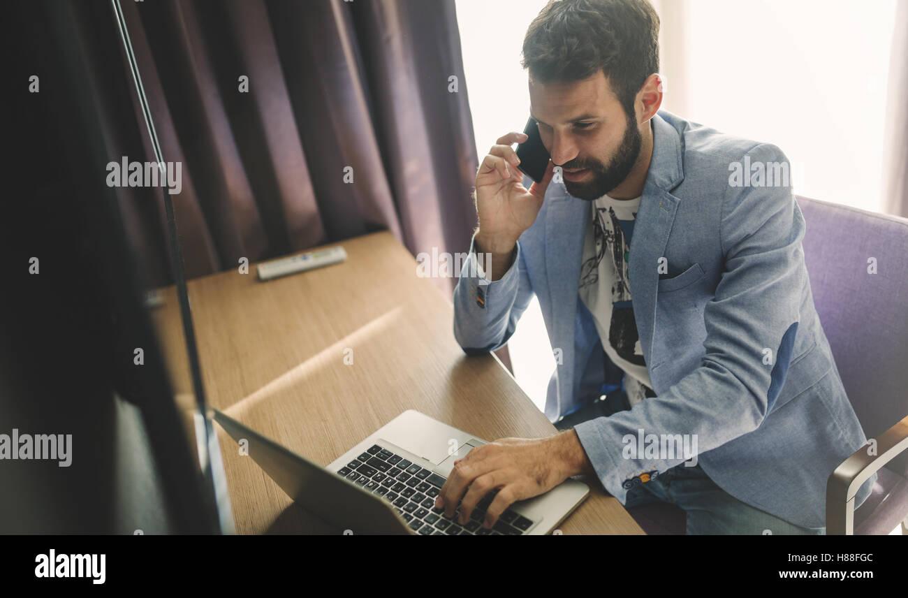 Empresario ocupado trabajando desde casa en portátil y teléfono Imagen De Stock
