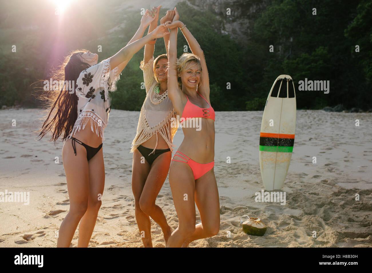 Feliz amigas de fiesta en la playa y el baile. Las mujeres divirtiéndose en la fiesta en la playa. Imagen De Stock
