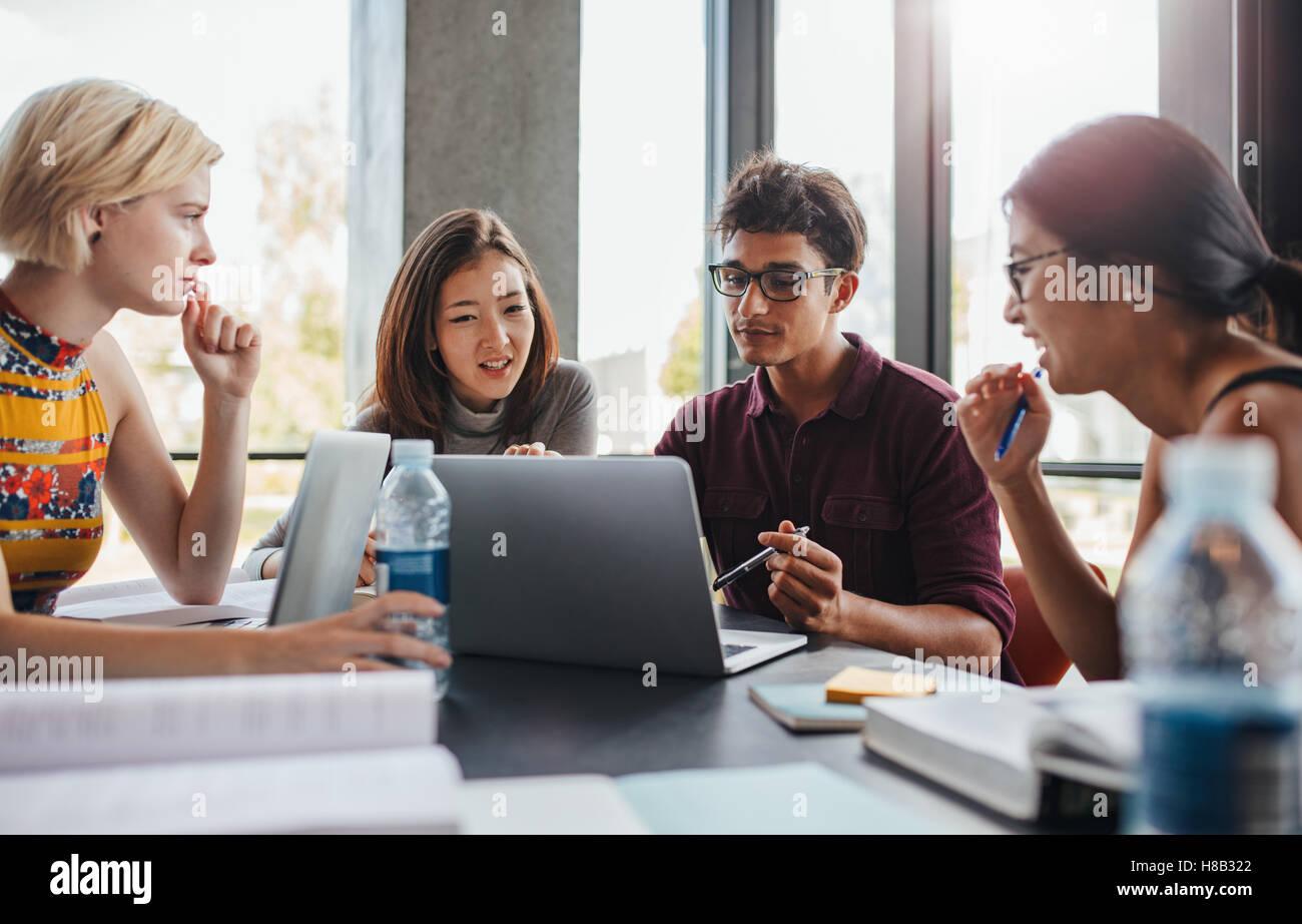 Los jóvenes que hacen grupo multirracial en la mesa de estudio. Estudiantes universitarios sentados juntos Imagen De Stock