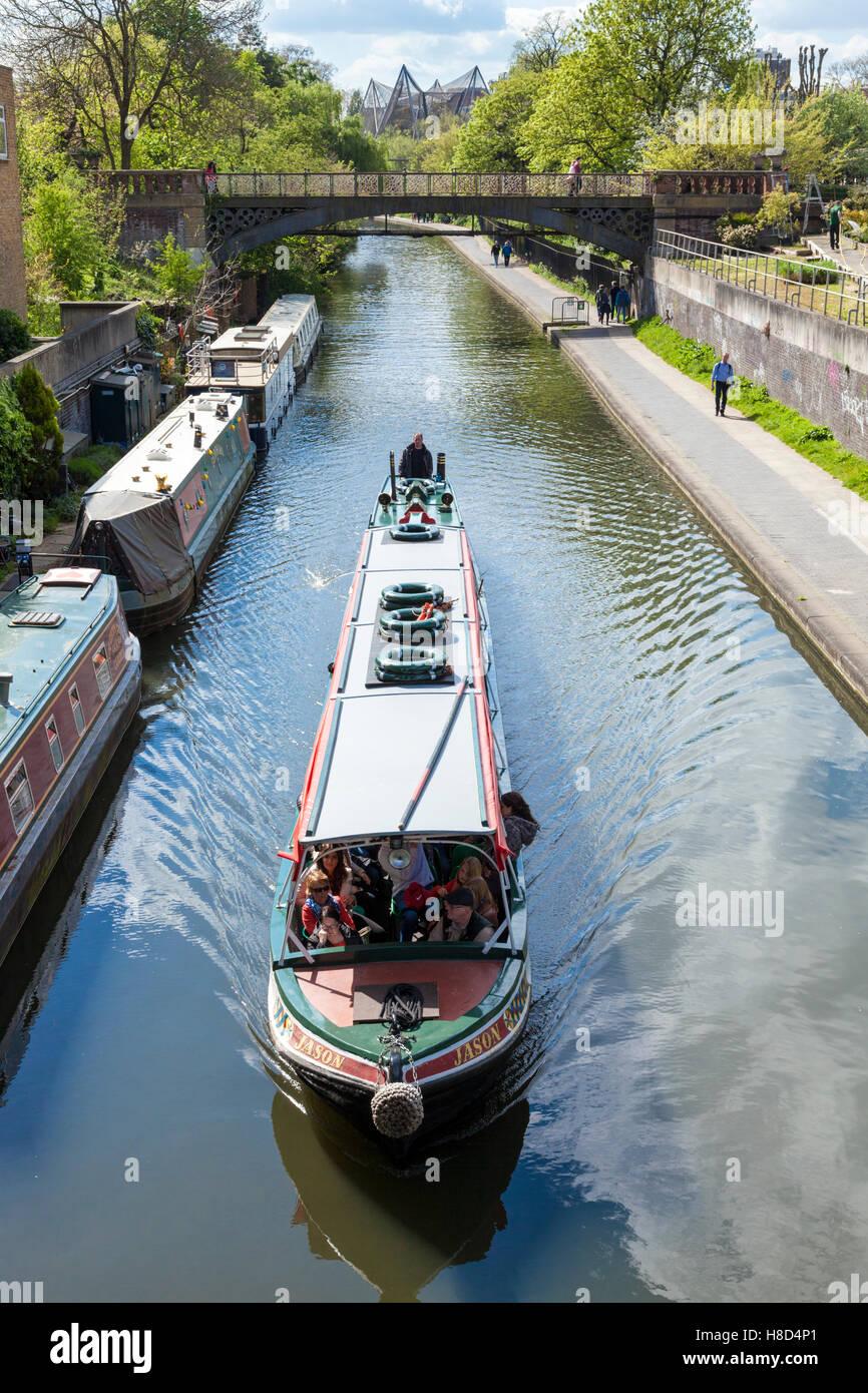 Los turistas en un viaje en barco al canal pasando amarrado narrowboats en Regent's Canal, Londres, Inglaterra, Imagen De Stock