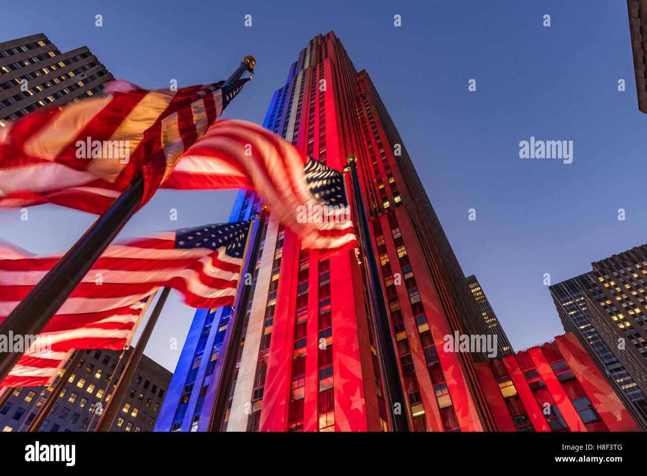 El Rockefeller Center en la penumbra iluminado en blanco, rojo y azul. Trampilla de banderas americanas en el viento. Imagen De Stock