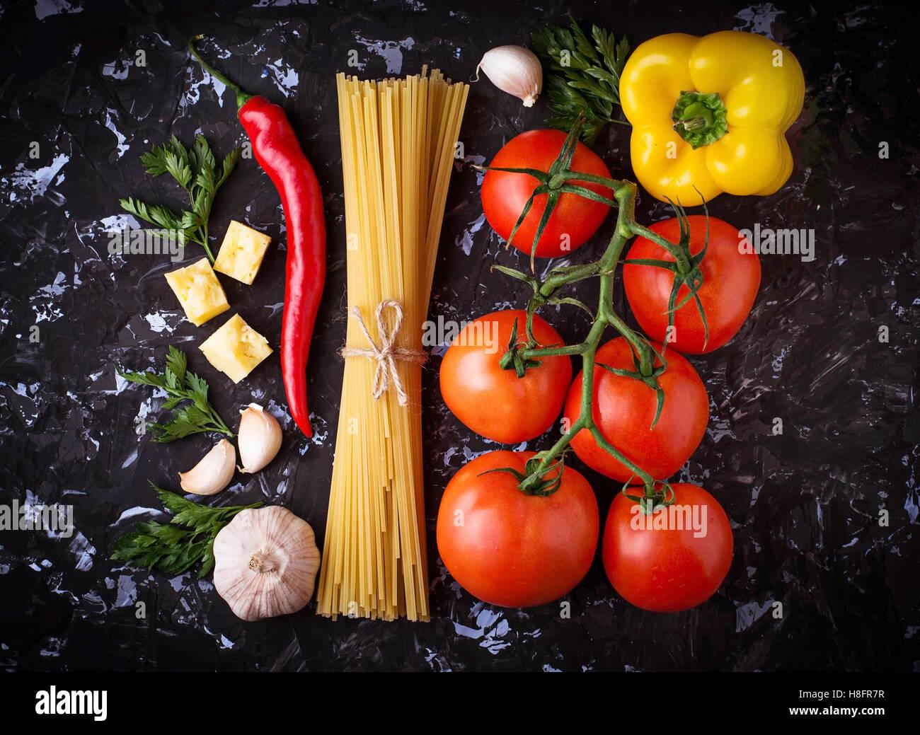 Concepto de comida italiana. Pasta, aceite de oliva, tomate, pimiento, perejil y queso. El enfoque selectivo. Vista Imagen De Stock